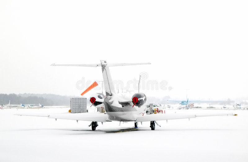 Airport white-out. Luxury business jet snowed in at an airport stock photo