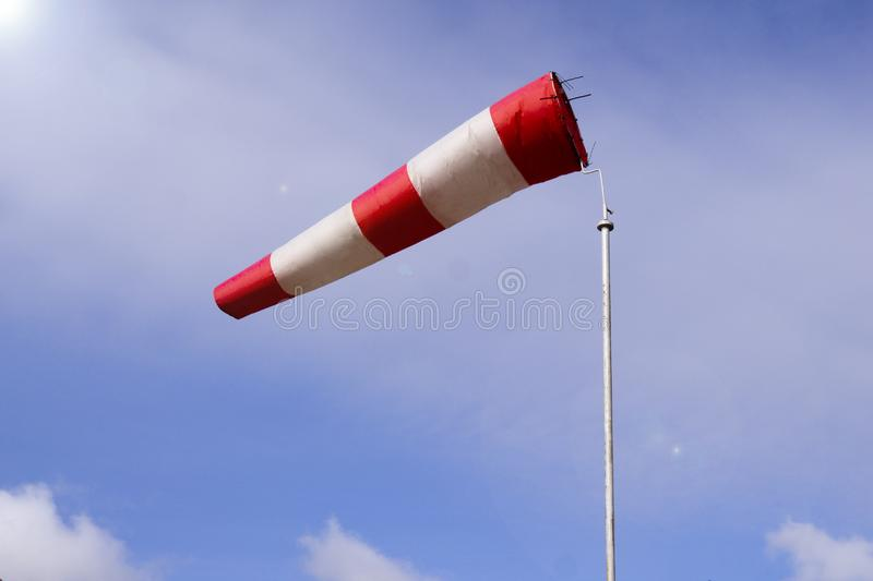 Airport windsock on clear blue sky background in windy weather indicate the local wind direction also called: air sock, drogue, stock images
