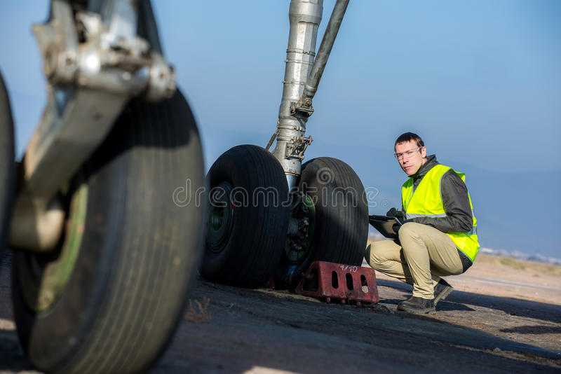 Airport worker checking chassis. Male engineer checking airplane's wheels before flight royalty free stock photos