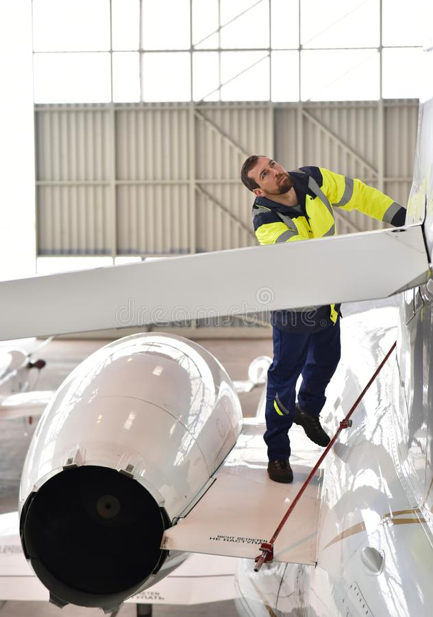 Airport workers check an aircraft for safety in a hangar. Closeup photo royalty free stock photo
