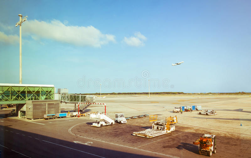 Airport workers receiving luggage and plane taking. Airport workers receiving luggage transport in the airstrip and a airplane taking off in the background royalty free stock photography