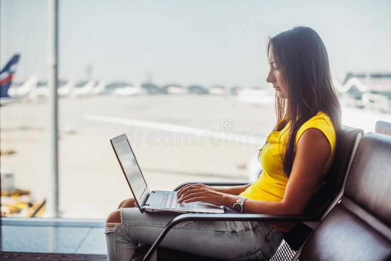 Airport. Young woman using laptop typing keyboard stock images