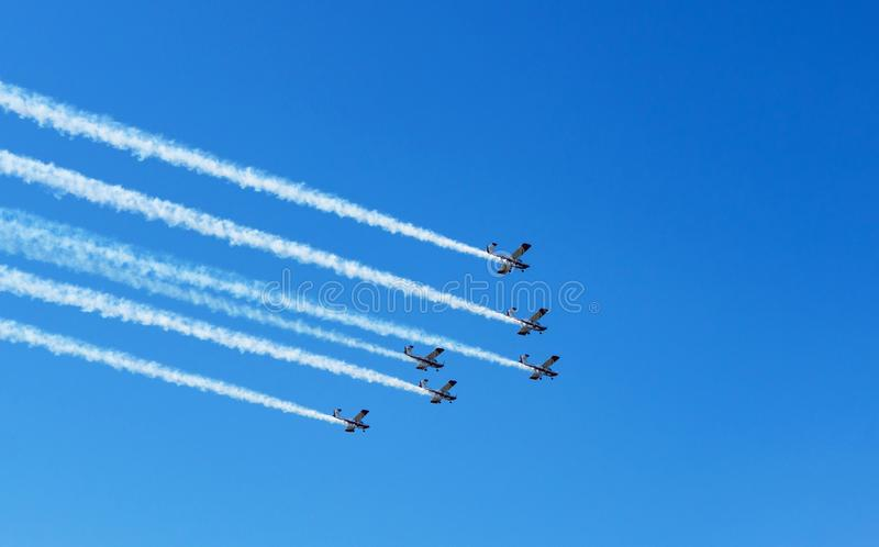 Airshow. White smoke trail of six planes on the blue sky stock photos