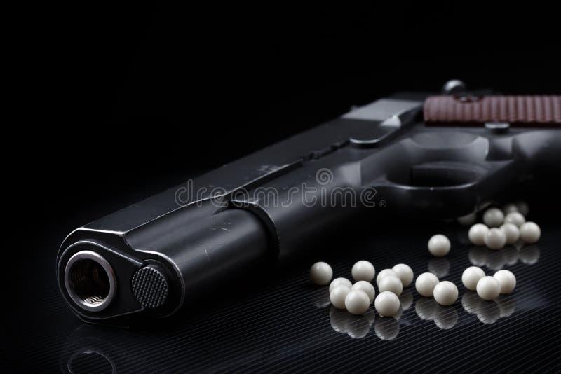 Airsoft手枪用黑光滑的表面上的bb子弹 库存照片