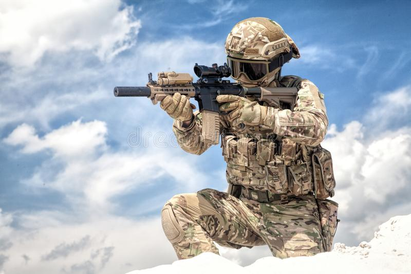 Airsoft game participant aiming with rifle replica. Fully equipped with tactical ammunition airsoft player in military camouflage uniform, aiming with optical royalty free stock photo