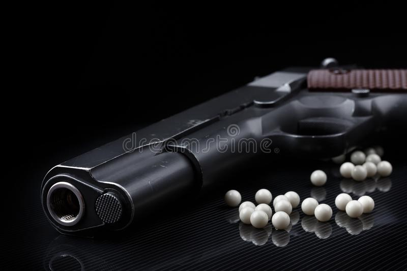 Airsoft pistol with bb bullets on black glossy surface stock photo