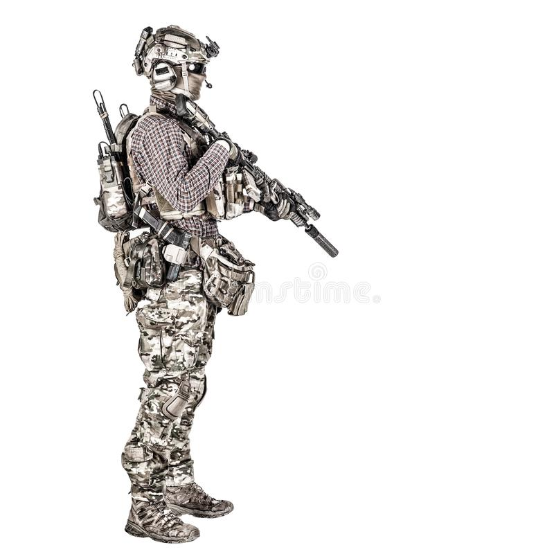 Airsoft player aiming service rifle studio shoot. Full length portrait of airsoft player in checkered shirt, wearing camouflage uniform, helmet with tactical royalty free stock photography