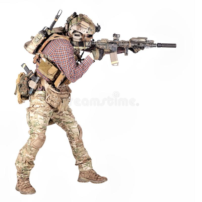 Airsoft player aiming service rifle studio shoot. Full length portrait of airsoft player in checkered shirt, wearing camouflage uniform, helmet with tactical stock photos