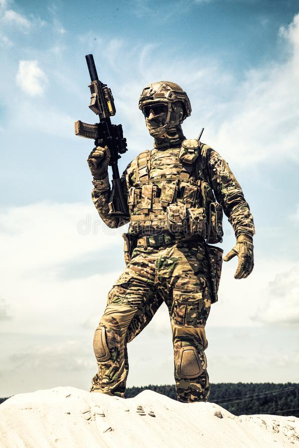 Airsoft player witt gun taking part in war games. Man in military camouflage uniform and mask, equipped tactical ammunition, standing on sand dune with service stock photography