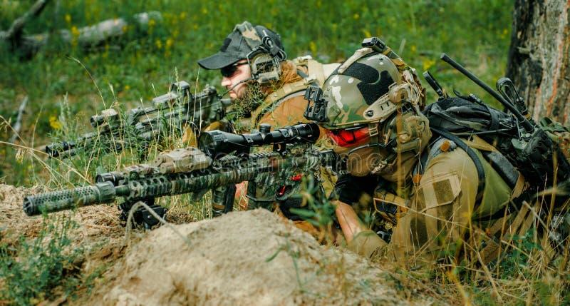 Airsoft prickskyttmän med vapen lägger på kullen Prickskytt och aimer på operation arkivfoto