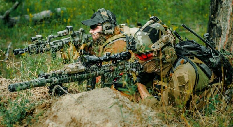Airsoft prickskyttmän med vapen lägger på kullen Prickskytt och aimer på operation royaltyfri bild