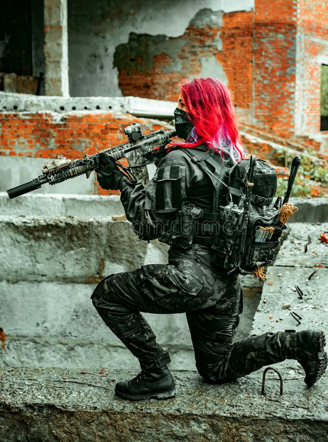 Free Airsoft Red-hair Woman In Uniform With Machine Gun Standing On Knee. Soldier On Ruine. Vertical Photo Side View Stock Image - 155804071