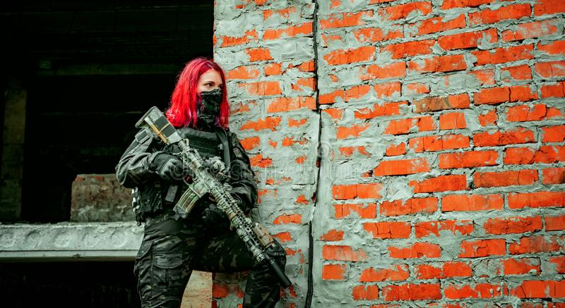 Airsoft red-hair woman in uniform with machine gun beside brick wall. Close up soldier on the ruins. Horizontal photo.  stock photo
