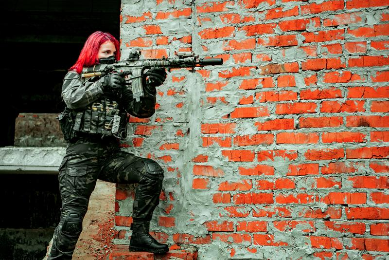 Airsoft red-hair woman in uniform with machine gun beside brick wall. Soldier aims at the sight on the ruins. Horizontal photo.  royalty free stock image