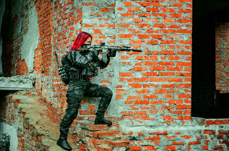 Airsoft red-hair woman in uniform with machine gun beside brick wall. Soldier aims at the sight on the ruins. Horizontal photo. Side view stock image