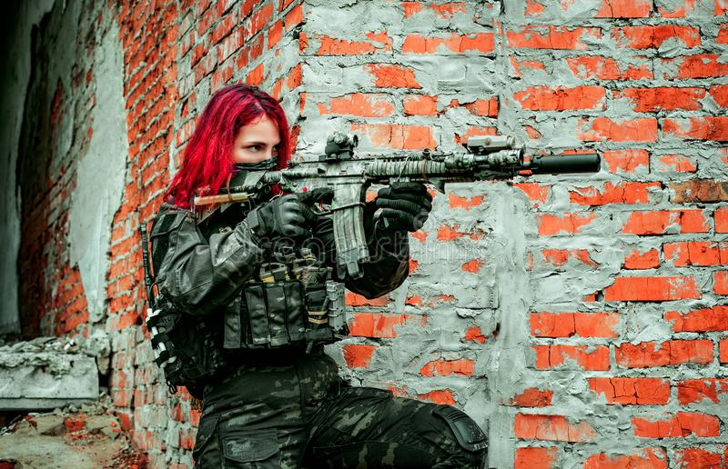 Airsoft red-hair woman in uniform with machine gun beside brick wall. Soldier aims at the sight on the ruins. Side view royalty free stock images