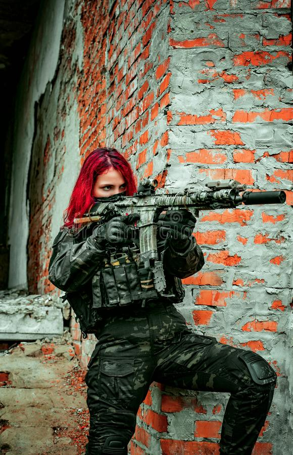 Airsoft red-hair woman in uniform with machine gun beside brick wall. Soldier aims at the sight on the ruins. Vertical photo stock photos