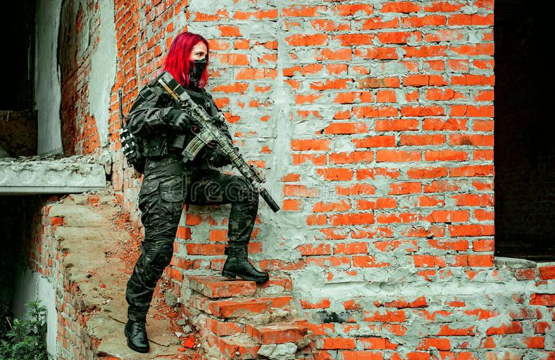 Airsoft red-hair woman in uniform with machine gun beside brick wall. Soldier on the ruins. Horizontal photo.  royalty free stock image