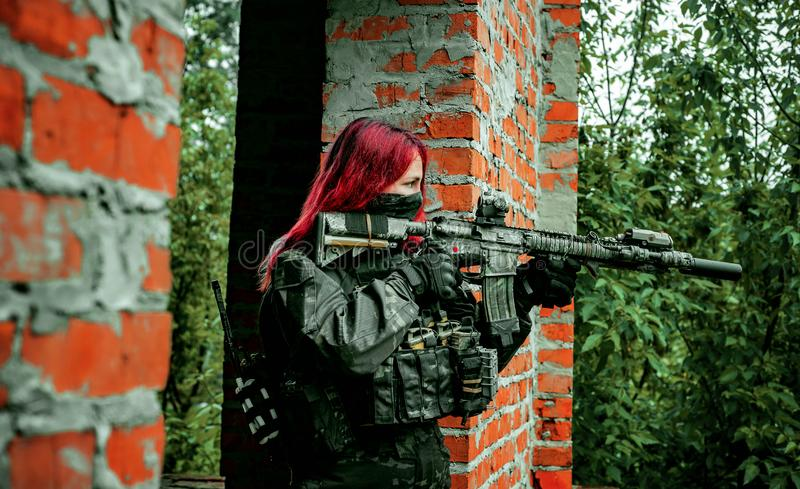 Airsoft red-hair woman in uniform with machine gun between brick walls. Soldier aims at the sight on the ruins. Horizontal photo. Side view royalty free stock photo