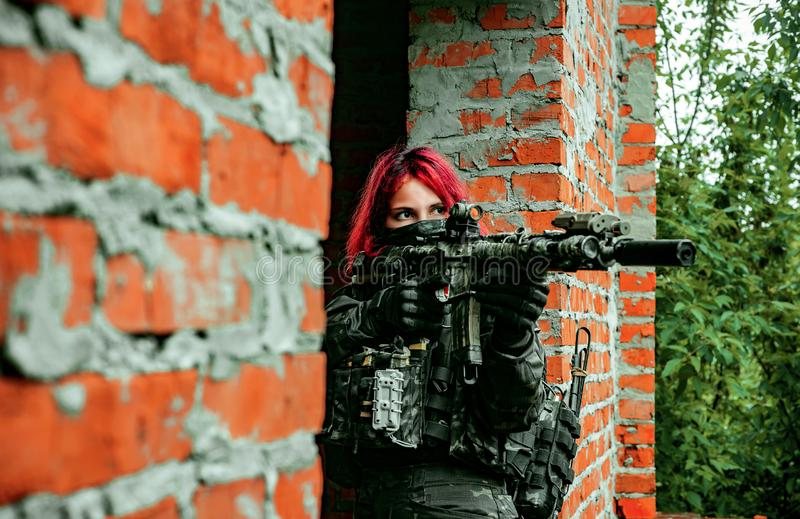 Airsoft red-hair woman in uniform with machine gun between brick walls. Soldier aims at the sight on the ruins. Horizontal photo.  stock photo