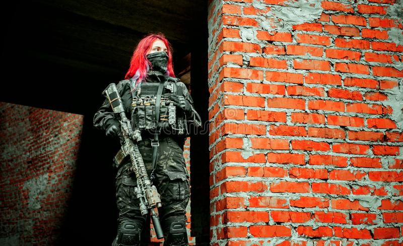 Airsoft red-hair woman in uniform with machine gun standing on ruins. Horizontal photo.  royalty free stock images