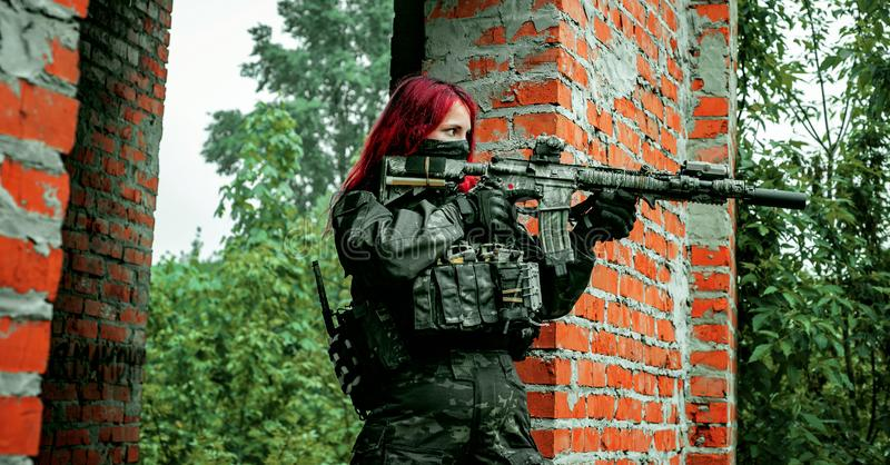 Airsoft red-hair woman in uniform with machine gun between walls. Soldier aims at the sight on the ruins. Horizontal photo side stock photography