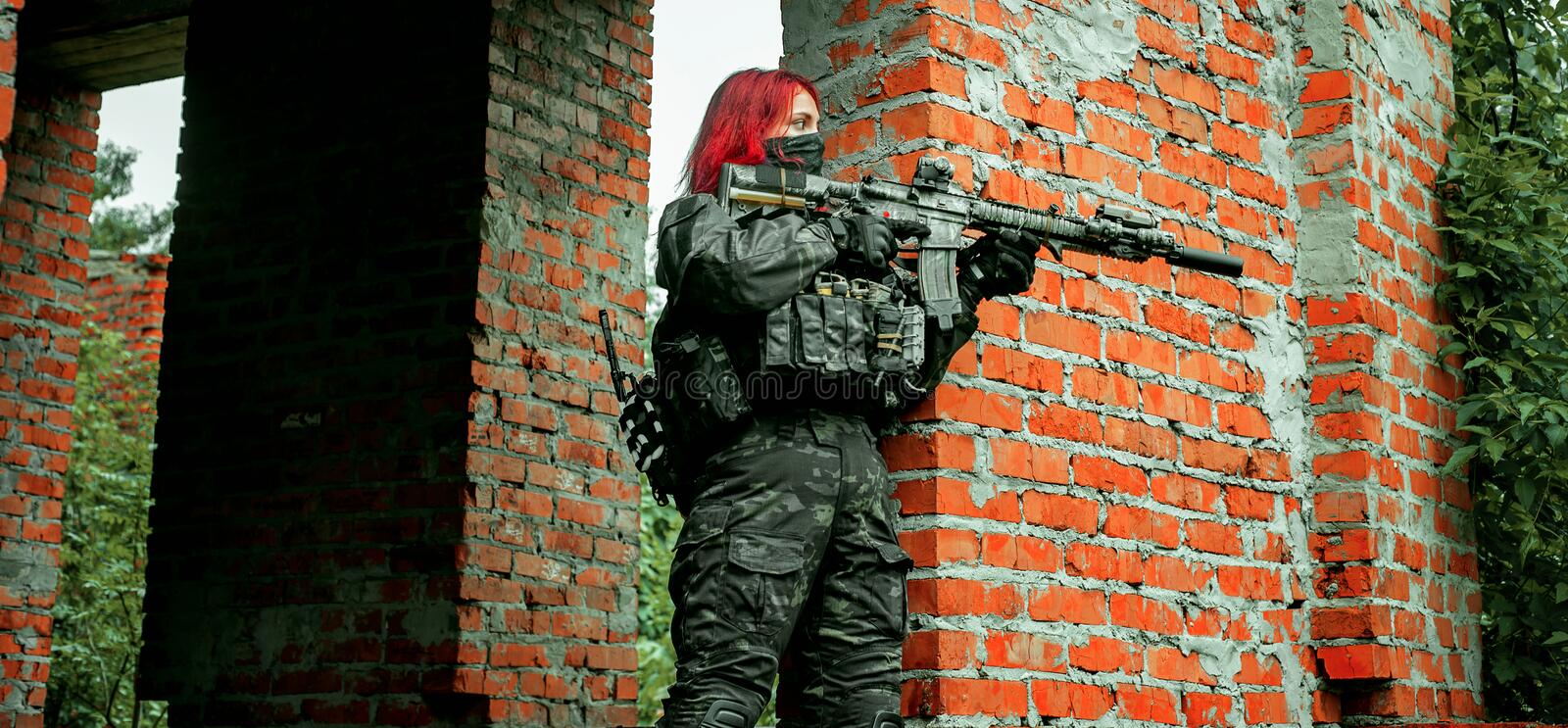 Airsoft red-hair woman in uniform with machine gun between walls. Soldier on the ruins. Horizontal photo side view royalty free stock image
