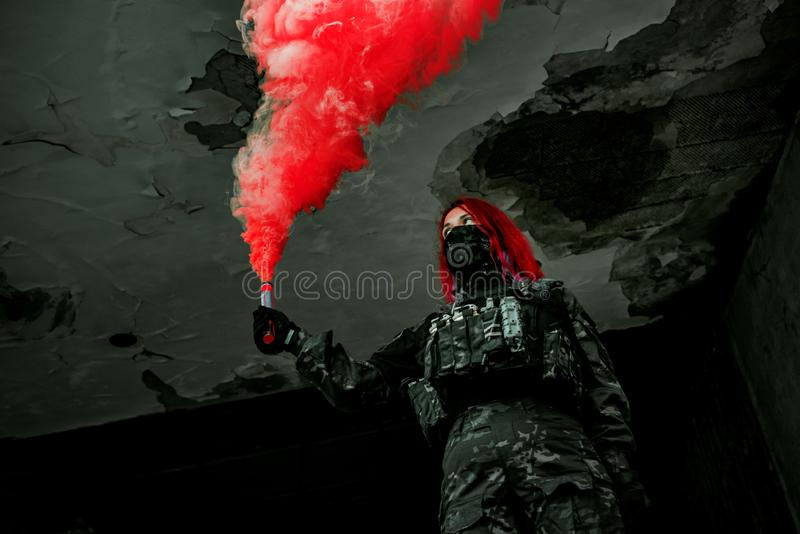 Airsoft red-hair woman in uniform with red smoke in hand. Close up soldier in broken building. Horizontal photo stock photo
