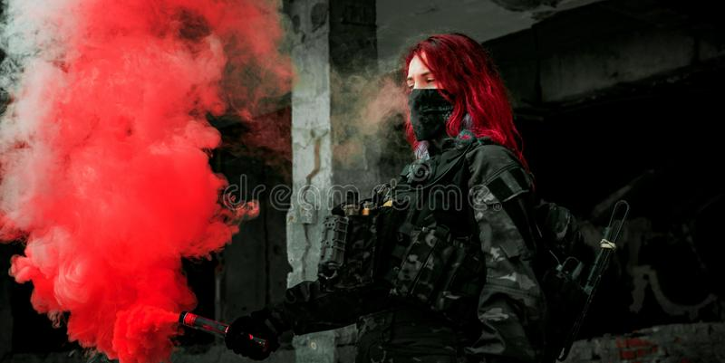 Airsoft red-hair woman in uniform with red smoke in hand. Close up soldier in broken building. Horizontal photo.  royalty free stock photo