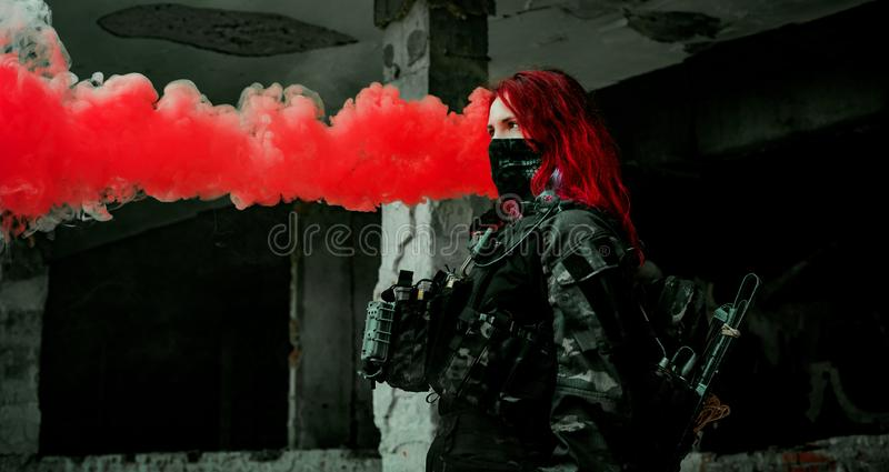 Airsoft red-hair woman in uniform with red smoke in hand. Close up soldier in broken building. Horizontal photo.  stock photos