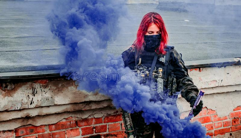 Airsoft red-hair woman in uniform with violet smoke on roof. Close up soldier. Horizontal photo.  royalty free stock image