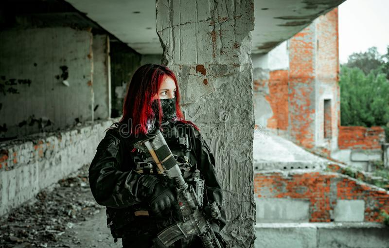 Airsoft red-head woman in uniform and put down machine gun. Close up soldier standing on balkony. Horizontal photo.  royalty free stock image