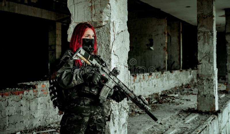 Airsoft red-head woman in uniform and put down machine gun. Close up soldier standing on balkony. Horizontal photo.  royalty free stock photo