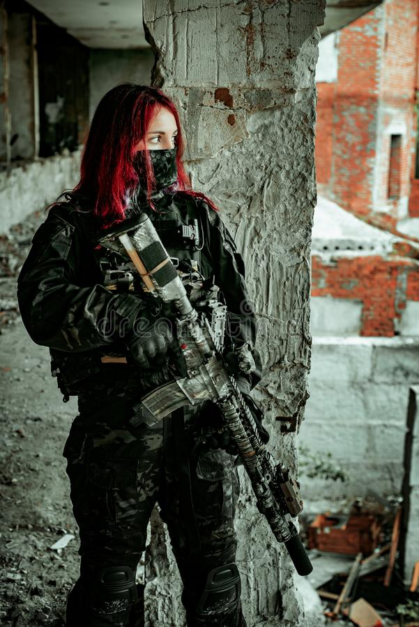 Airsoft red-head woman in uniform and put down machine gun. Close up soldier standing on balkony. Horizontal photo side view.  royalty free stock images