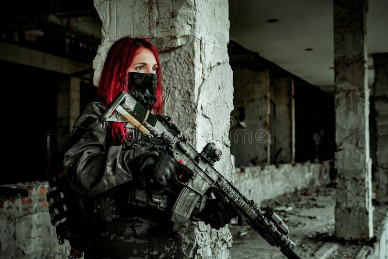 Airsoft red-head woman in uniform and put down machine gun. Close up soldier standing on balkony. Horizontal photo side view.  royalty free stock photo
