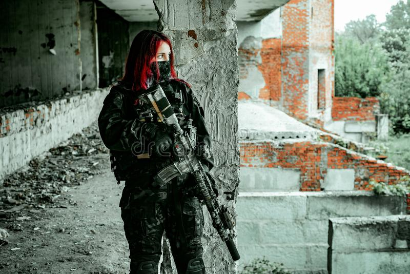 Airsoft red-head woman in uniform and put down machine gun. Soldier standing on balkony. Horizontal photo.  royalty free stock image