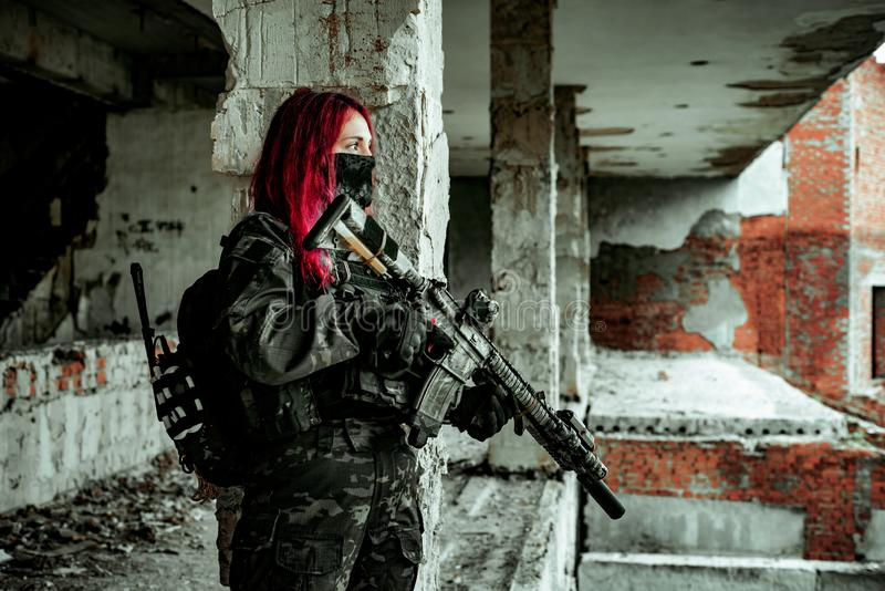 Airsoft red-head woman in uniform and put down machine gun. Soldier standing on balkony. Horizontal photo side view.  stock photography