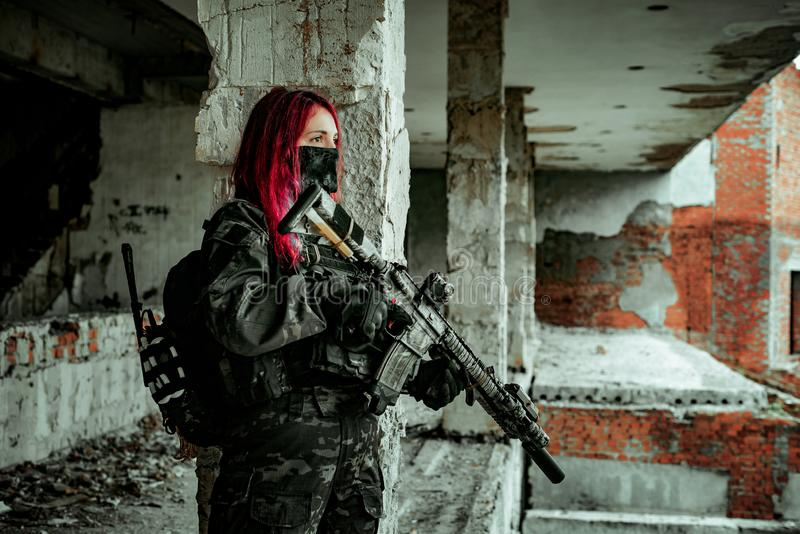 Airsoft red-head woman in uniform and put down machine gun. Soldier standing on balkony. Horizontal photo side view.  royalty free stock images