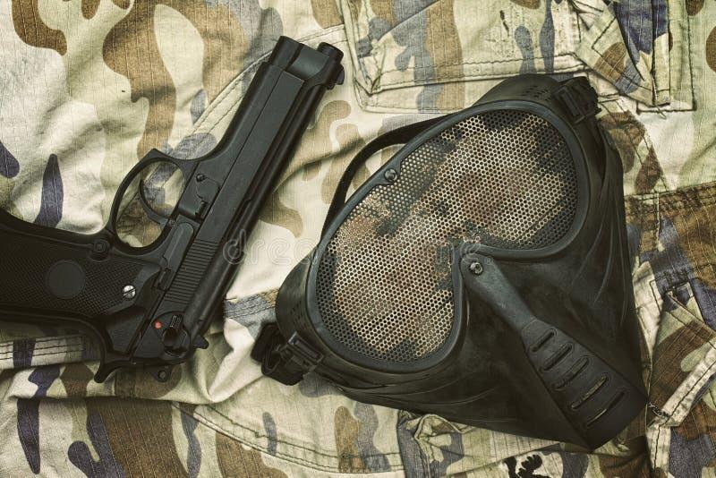 Airsoft skyddsmaskering, terroristmaskering och 9mm pistol royaltyfri foto