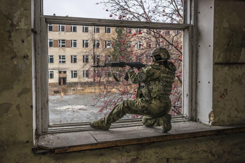Airsoft snajper przy okno Przeciw tłu ruiny budynki obraz royalty free