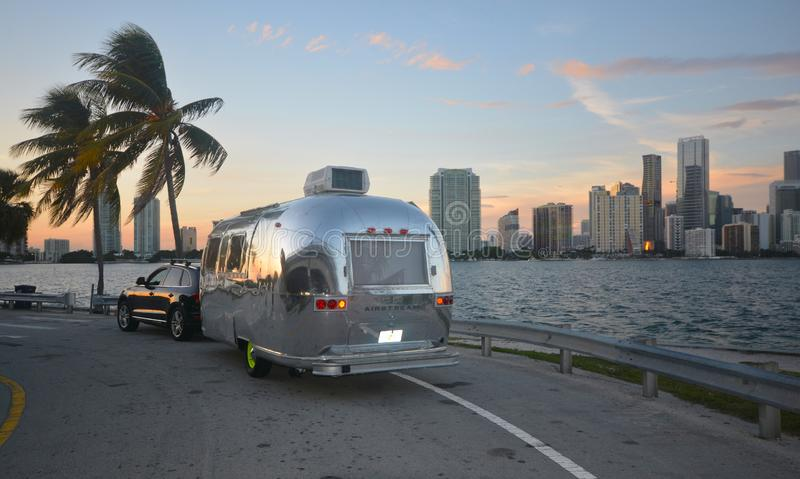 Airstream in Miami. A beautiful, classic chrome Airstream camper was parked overlooking the Miami, Florida skyline. A great sunset accented the soft pastels in stock image