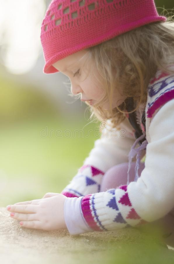 Airy backlit Fall close up shot of adorable girl in knitwear and red hat playing in sand. Shallow depth of field headshot of a cute girl playing alone in sand stock photo