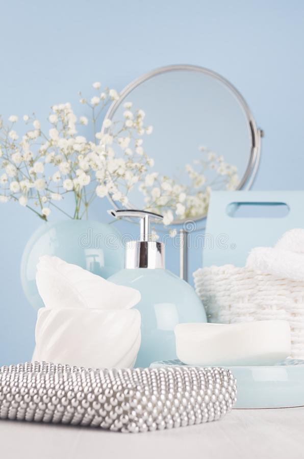 Airy blue dressing table with cosmetic accessories, mirror, basket, towel, silver bag, flowers and ceramic bowls on white wood. royalty free stock photography