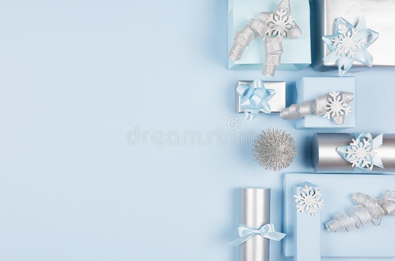 Airy soft cold winter season celebration background in pastel blue and silver color with different gift boxes as decorative border. Top view stock photography