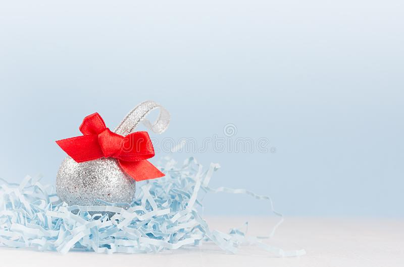 Airy soft light christmas minimalist background - silver small ball with red bow on white and pastel blue backdrop, copy space. Airy soft light christmas royalty free stock images