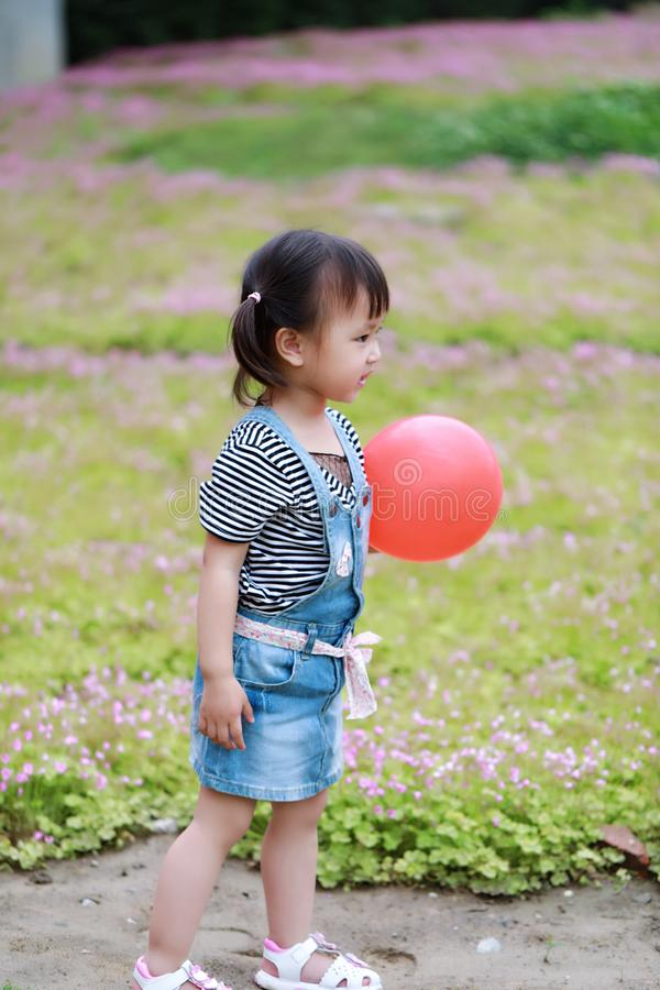 Aisa cute naughty lovely adorable child girl play with balloon have fun outdoor in summer park happy smile happiness childhood stock photo