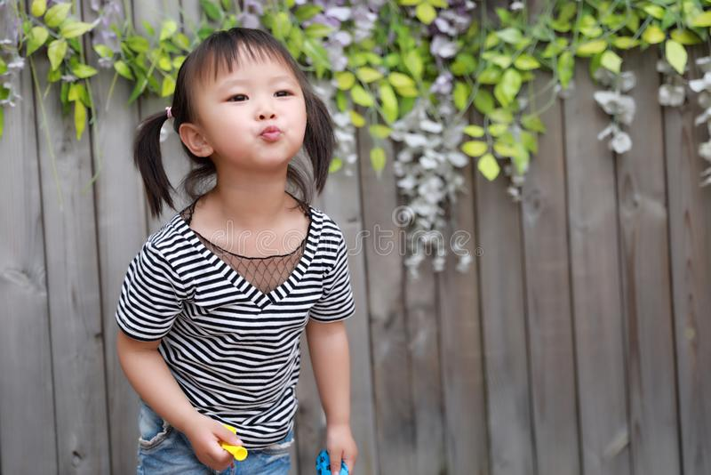 Aisa cute naughty lovely adorable child girl play with balloon kiss camera outdoor in summer park happy smile happiness childhood stock images