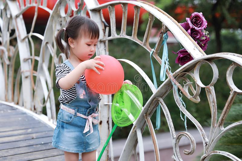 Aisa cute naughty lovely child girl play with balloon have fun outdoor in summer park happy smile happiness funny childhood royalty free stock photography