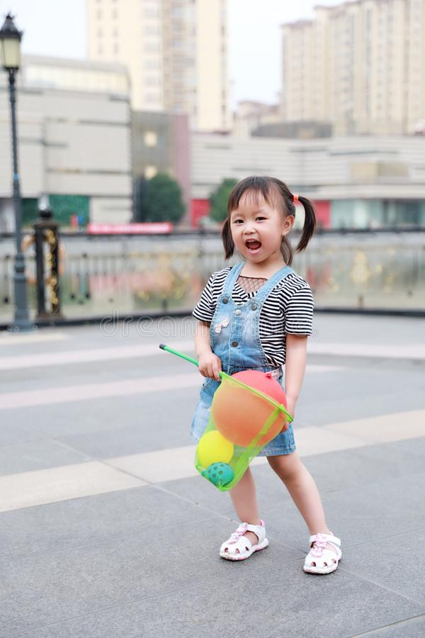 Aisa cute naughty lovely child girl play with balloon have fun outdoor in summer park happy smile happiness funny childhood royalty free stock images