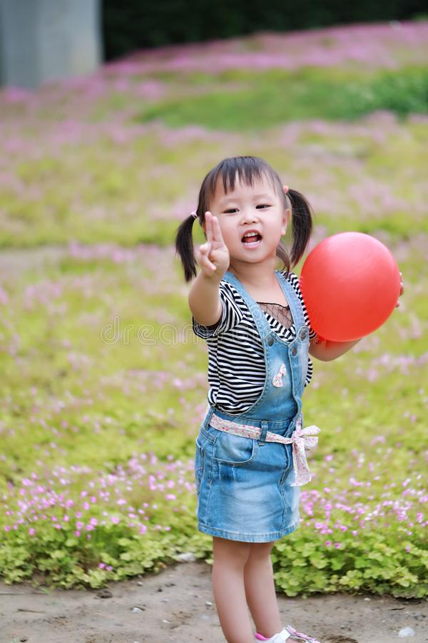 Aisa cute naughty lovely child girl with V pose play with balloon have fun outdoor in summer park happy smile happiness childhood stock photography